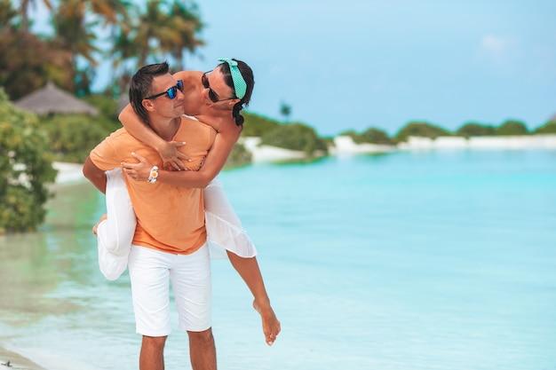 Família jovem na praia de areia branca durante as férias de verão