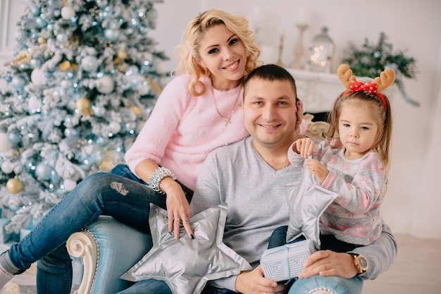 Família jovem no fundo da árvore de natal