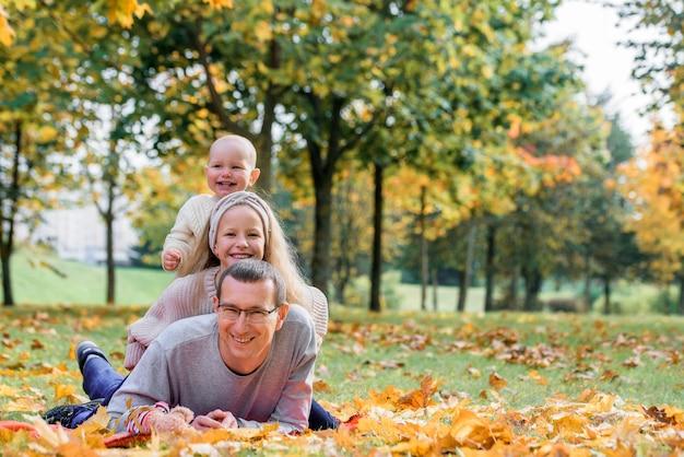 Família jovem no parque outono deitado sobre folhas amarelas.