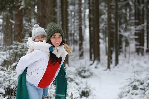Família jovem para passear. mãe e filha estão caminhando em um parque de inverno.