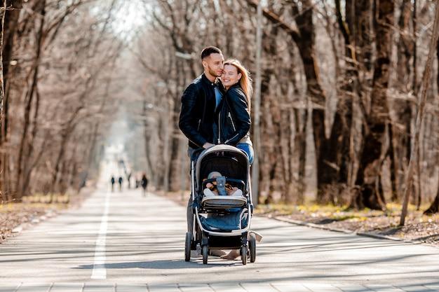 Família jovem passeio no parque na primavera com uma criança em um carrinho. pais felizes