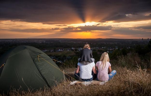 Família jovem perto da tenda, apreciando um belo pôr do sol