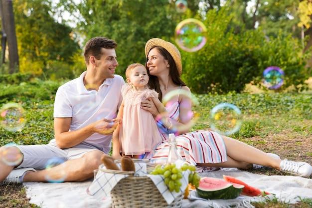 Família jovem positiva com uma menina passando um tempo juntos