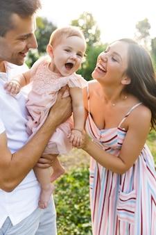 Família jovem rindo com a garotinha passando um tempo juntos