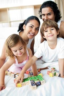 Família jovem se divertindo com blocos alfabéticos