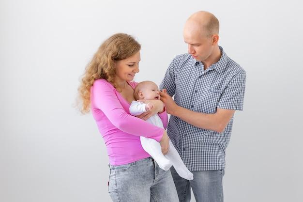 Família jovem segurando um bebê na parede branca