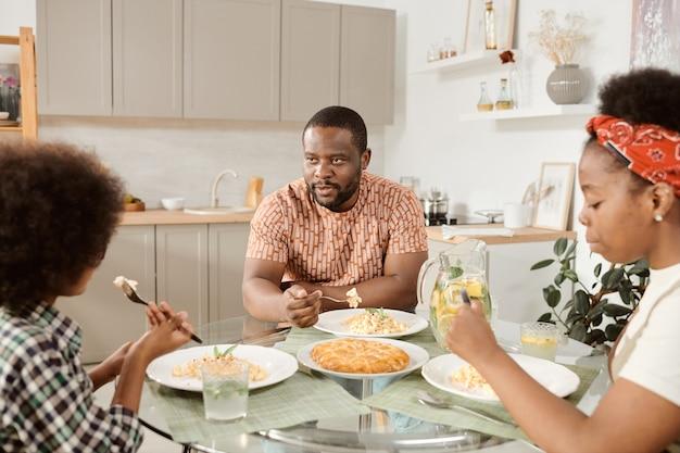 Família jovem sentada à mesa servida e jantando na cozinha
