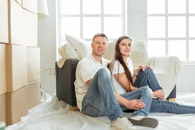 Família jovem sentada no chão da nova sala de estar.