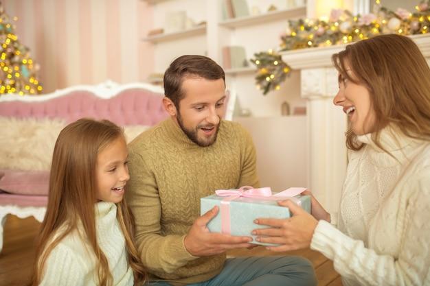 Família jovem sentada no chão trocando presentes de natal