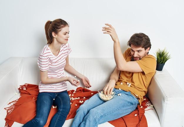 Família jovem sentada no sofá com pipoca assistindo filmes