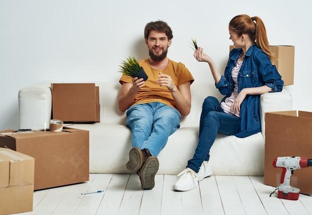 Família jovem sentada no sofá, desempacotando coisas para a inauguração de casa. foto de alta qualidade