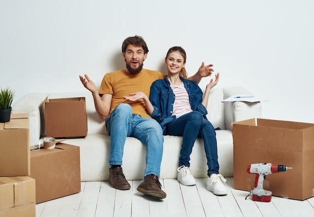 Família jovem sentada no sofá desempacotando coisas para a inauguração de casa