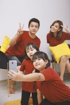 Família jovem sorridente com duas filhas pequenas faz auto-retrato na célula juntos pais felizes com filhos pequenos se divertem, tirem selfie no smartphone em casa