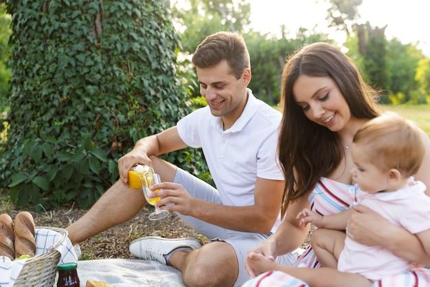 Família jovem sorridente com uma garotinha passando um tempo juntos
