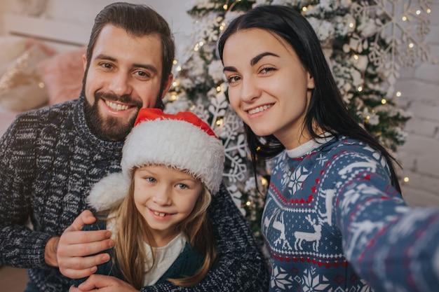 Família jovem sorridente na atmosfera de natal, fazendo foto com o smartphone.