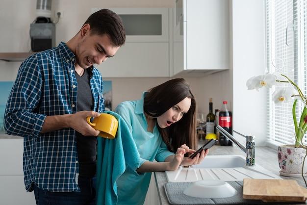 Família jovem. um homem esfrega uma xícara amarela, uma mulher chocada olhando para o telefone, notícias inesperadas