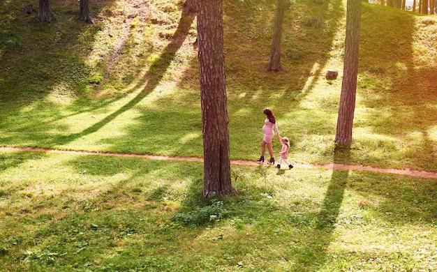 Família jovem, uma mãe grávida e sua filha mais velha estão andando em um parque da cidade de verão em tempo ensolarado