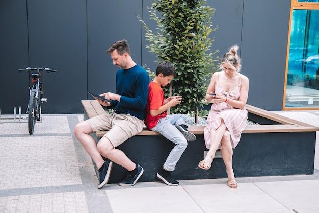 Família jovem usando tablet, smartphone em dia de verão na praça da cidade. conceito de tecnologia. foto de alta qualidade. estilo de vida