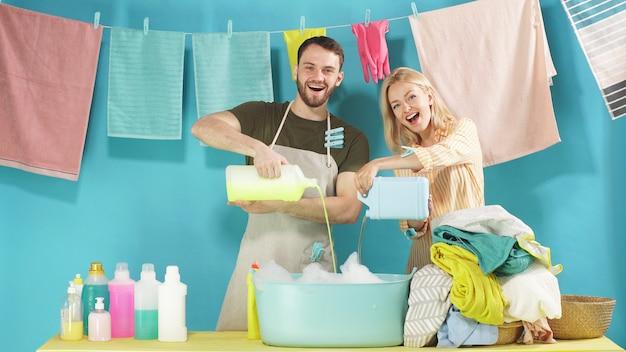 Família jovem vai lavar roupa. o marido e a esposa estão prontos para iniciar as tarefas domésticas.