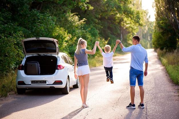 Família jovem viaja de carro. pai, mãe e filho fazem uma pausa antes de dirigir um carro e caminhar.
