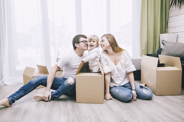 Família junta feliz jovem linda com um bebezinho se muda com caixas para uma nova casa