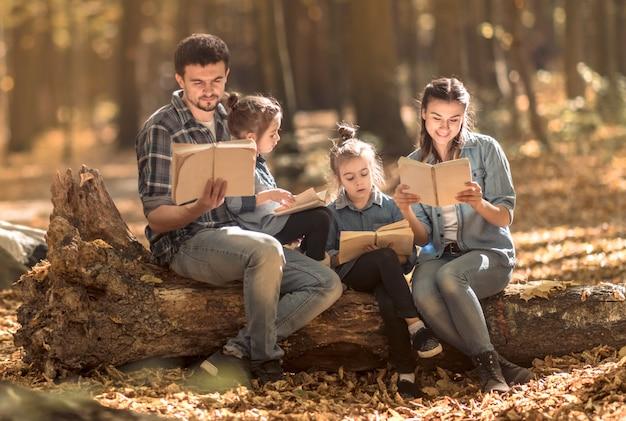 Família junto lendo livros na floresta.
