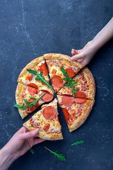 Família lanche, mãe e criança mãos tomando fatias de pizza de calabresa. almoço ou jantar tradicional italiano. fast-food e comida de rua conceito.