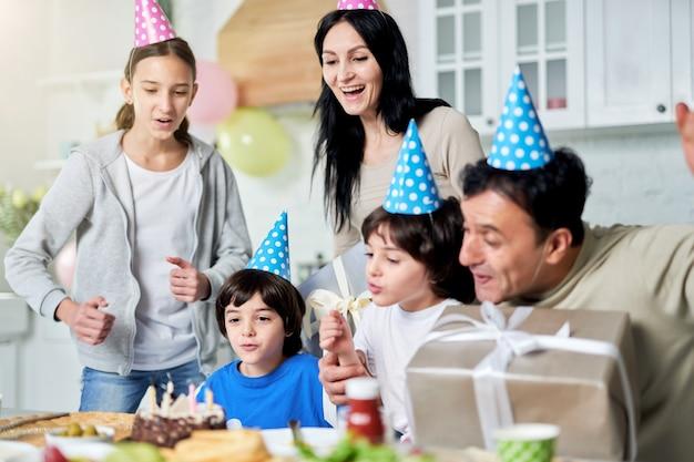 Família latina alegre com crianças usando bonés de aniversário, comemorando o aniversário juntos em casa. família feliz, conceito de celebração. foco seletivo