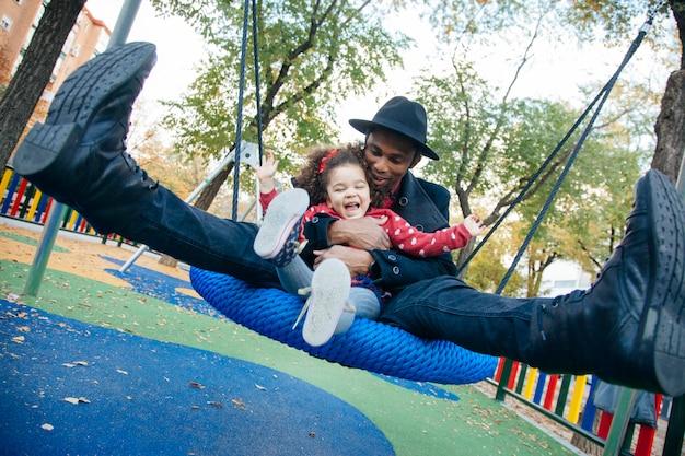 Família latina balançando em um parque de crianças de rua