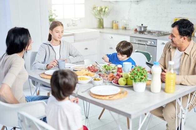 Família latina feliz desfrutando a refeição juntos, sentados à mesa na cozinha em casa. infância, conceito de alimentação