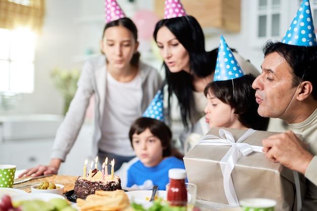 Família latina próxima com crianças usando bonés de aniversário, soprando velas em um bolo enquanto comemoram o aniversário juntos em casa. foco seletivo