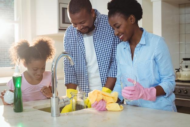 Família lavar utensílios na pia da cozinha