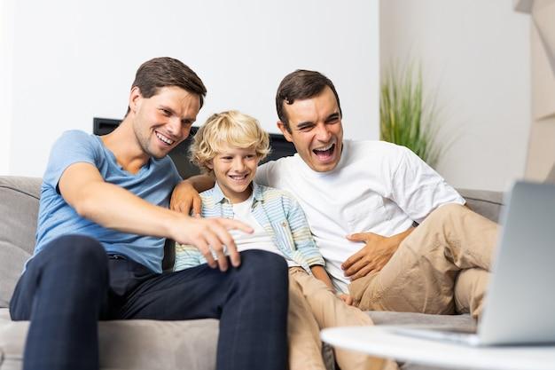 Família lgbt, casal gay com filho adotivo - pais homossexuais com filho se divertindo em casa