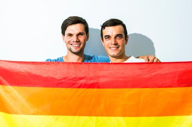 Família lgbt, casal gay segurando uma bandeira do arco-íris