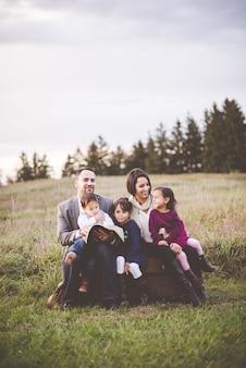 Família linda e alegre com mãe, pai e três filhos lendo a bíblia no parque