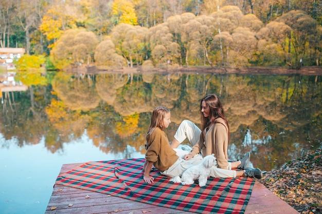 Família linda em dia quente de outono perto do lago