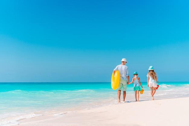 Família linda feliz em umas férias de praia tropical