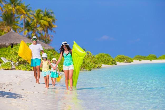 Família linda feliz na praia branca com colchões de ar e brinquedos infantis