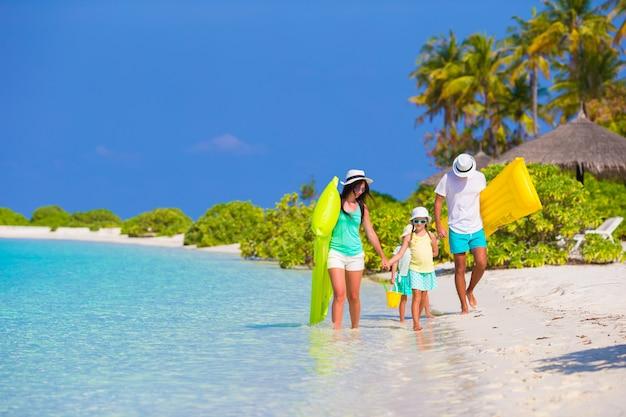 Família linda feliz na praia branca com colchões de ar