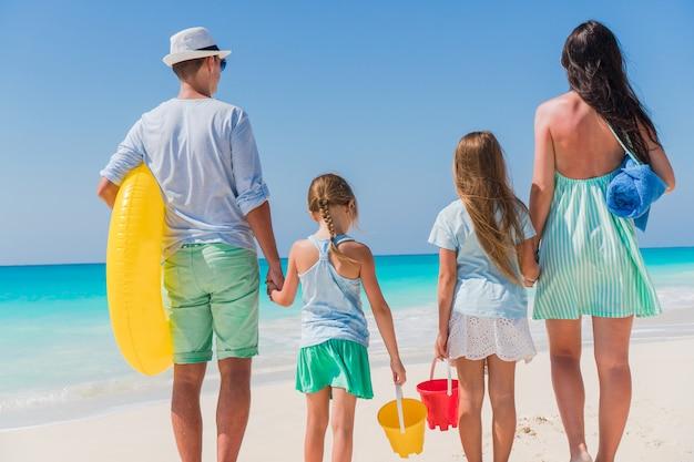 Família linda feliz na praia branca se divertindo