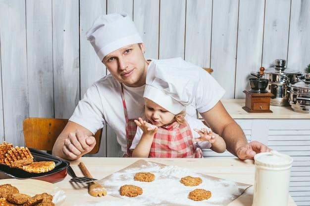 Família, linda filha pai em casa na cozinha rindo e preparando comida juntos