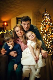 Família linda jovem com dois filhos posando em uma cadeira em um interior de natal
