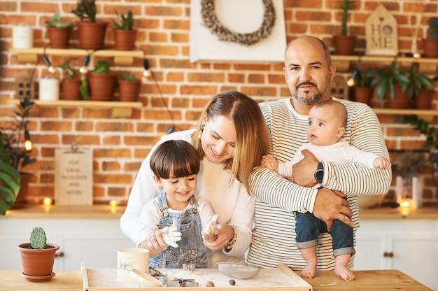 Família linda jovem se divertindo e cozinhando na cozinha ensolarada