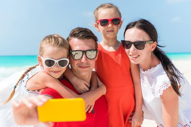Família linda jovem tirando retrato de selfie na praia