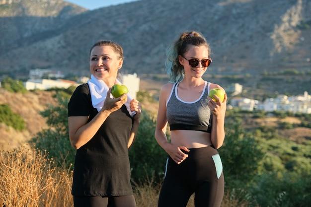 Família mãe e filha adolescente em roupas esportivas, comendo maçãs após o exercício, correndo na natureza, dia de sol nas montanhas