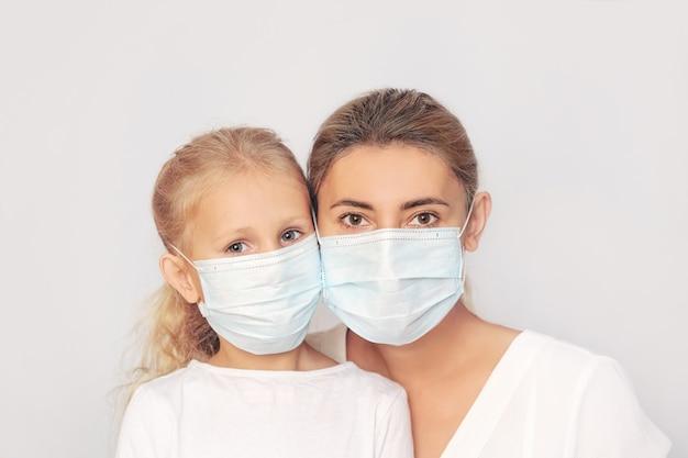 Família mãe e filha com máscaras médicas juntas em um fundo isolado