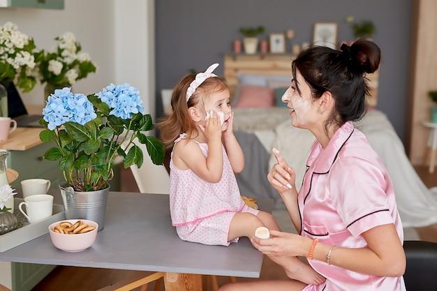 Família mãe e filha de manhã tomar café na cozinha