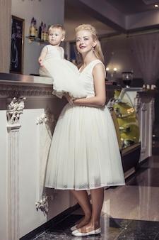 Família, mãe e filha elegantes e bem vestidas, lindas e felizes juntas
