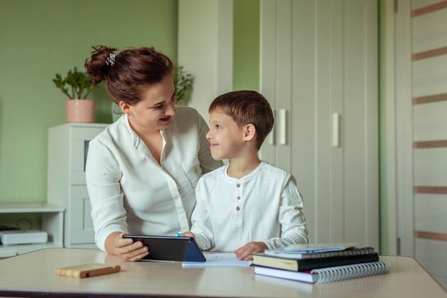 Família mãe e filho com alegria fazendo lição de casa na sala usando tablet