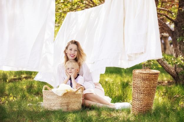 Família mãe e filho lindos e felizes juntos penduram roupas limpas no jardim